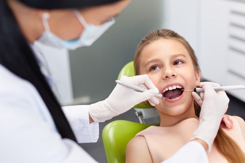 Teeth checkup at dentist's office. Dentist examining girls teeth in the dentists chair